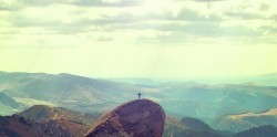 person spreading her arms to the sky at the top of a mountain, seen from very far