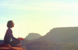 person meditating facing the sun, sitting on top of natural rock formation