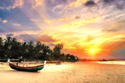sunrise on beach with wooden boat in the sand