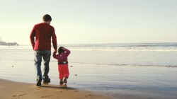 father and small child daughter waling in beach holding hands