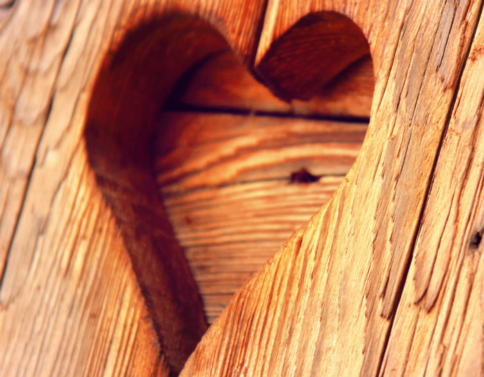 heart shaped carving into wood surface of furniture