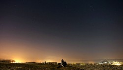 man sitting on a field looking at the starry night sky