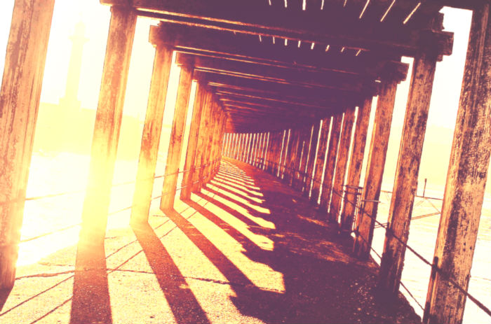 Covered pier pathway with sunshine behind it