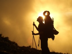 woman climbing mountain with gear at her back and sun shining behind her