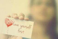 woman holding paper card saying love yourself first