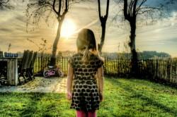 girl in closed-in backyard contemplating the sun