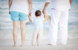 couple at beach holding hands with child