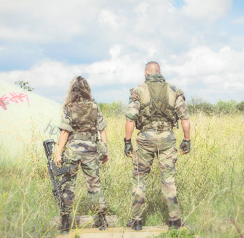 army woman and man standing side by side seen from behind